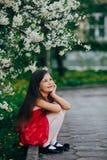 Hübsches Mädchen, das unter dem Kirschbaum sitzt Stockbild