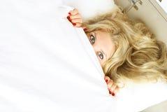 Hübsches Mädchen, das unter der Decke sich versteckt Lizenzfreie Stockfotos