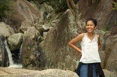 Hübsches Mädchen, das vor Wasserfall im KOH Samui, Thailand lächelt Stockfotografie