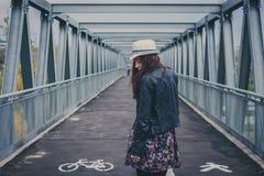 Hübsches Mädchen, das weg auf eine Brücke geht Lizenzfreie Stockfotos