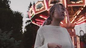 Hübsches Mädchen in den Gläsern rüttelt Haar nahe Karussellanziehungskraft in amusment Park stock video