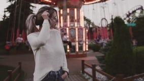Hübsches Mädchen in den Gläsern streicheln Haar nahe Karussellanziehungskraft in amusment Park stock video footage