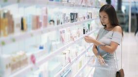 Hübsches Mädchen in den Kosmetik kaufen wählt Gesichtscreme, einsetzt sie in Korb, Zeitlupe stock video footage