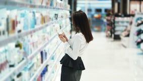 Hübsches Mädchen in den Kosmetik kaufen wählt Gesichtscreme, liest Bestandteile, Zeitlupe stock footage