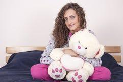 Hübsches Mädchen in den pajams, die einen Bären anhalten Lizenzfreie Stockbilder