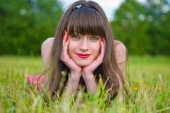 Hübsches Mädchen in den roten sarafan Lügen auf grünem Gras stockbilder