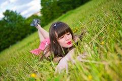 Hübsches Mädchen in den roten sarafan Lügen auf grünem Gras Lizenzfreie Stockfotografie