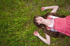 Hübsches Mädchen in den roten sarafan Lügen auf grünem Gras Lizenzfreie Stockbilder