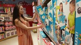 Hübsches Mädchen in den Spielwaren kaufen stock video