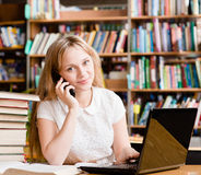 Hübsches Mädchen in der Bibliothek schreibend auf Laptop und am Telefon sprechend Lizenzfreie Stockfotografie