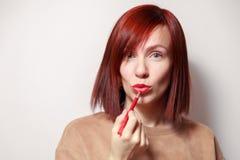 Hübsches Mädchen der Nahaufnahmeporträt-Rothaarigen malt ihre Lippen mit rotem Bleistiftlippenstift Konzeptschule des Makes-up, z stockbild