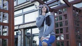 Hübsches Mädchen in der warmen stilvollen Kleidung, die auf dem Yard aufwirft 4K stock footage