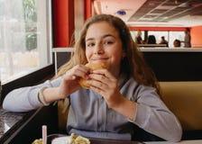 Hübsches Mädchen des jungen jugendlich mit einem Appetit einen Hamburger in einem Café essend lizenzfreie stockfotografie
