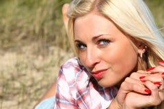 Hübsches Mädchen des Nahaufnahmeportraits, das auf Strand liegt Lizenzfreies Stockbild
