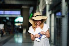 Hübsches Mädchen in einem breitrandigen Hut mit dem Pass und Karten in einer Hand Lizenzfreies Stockfoto