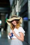 Hübsches Mädchen in einem breitrandigen Hut mit dem Pass und Karten in einer Hand Lizenzfreie Stockbilder