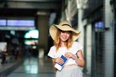 Hübsches Mädchen in einem breitrandigen Hut mit dem Pass und Karten in einer Hand Lizenzfreies Stockbild