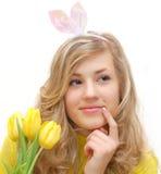 Hübsches Mädchen im Esterhäschenkostüm mit Tulpen Lizenzfreies Stockbild