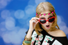 Hübsches Mädchen im Herzen formte Sonnenbrille auf Blau Stockfotografie