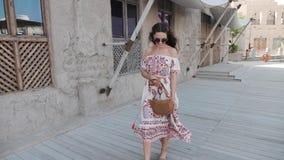 Hübsches Mädchen im Kittel geht Tänze durch Wand auf Pier an der Seebucht stock video
