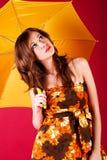 Hübsches Mädchen im Kleid mit einem Regenschirm lizenzfreies stockbild