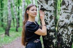 Hübsches Mädchen im schwarzen russischen Kleid mit Stickerei lehnte sich an der Birke Stockfotos