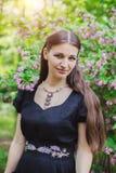 Hübsches Mädchen im schwarzen russischen Kleid mit Stickerei unter Blumen von Weigela lizenzfreie stockfotografie