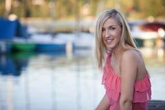 Hübsches Mädchen im sexy rosa Kleid, das auf Seeufer sitzt Stockbild