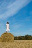 Hübsches Mädchen im weißen Kleid auf Heuschober auf dem Gebiet Lizenzfreie Stockfotos