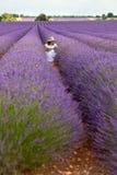 Hübsches Mädchen im weißen Kleid, das auf dem Blumengebiet des Lavendels sitzt, Stockfoto