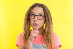 Hübsches Mädchen 12-13 Jahre alte Blondine mit dem gelockten Haar mit den Gläsern, Blicke nachdenklich beiseite, denkend an Schul Stockbilder