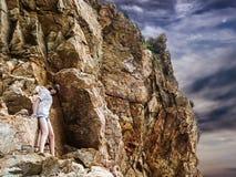 Hübsches Mädchen klettert einen Felsen und einen mysteriösen Himmel lizenzfreies stockfoto