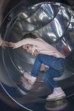 Hübsches Mädchen kriecht auf einem Dia im Spielplatz stockfoto