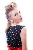 Hübsches Mädchen lustige junge blonde Pinupfrau im Tupfenkleid mit den Lockenwicklern, welche die Kameraschultern zurück lokalisie Stockfotos