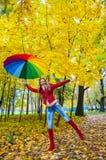 Hübsches Mädchen mit buntem Regenschirm im Herbstpark Stockfoto