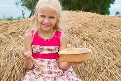 Hübsches Mädchen mit dem Brot, das auf einem Heuschober sitzt Stockfotos