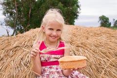 Hübsches Mädchen mit dem Brot, das auf einem Heuschober sitzt Lizenzfreie Stockfotografie