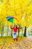 Hübsches Mädchen mit dem bunten Regenschirm, der in Herbstpark springt Stockbild