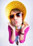 Hübsches Mädchen mit dem gelben Sommerhut, der einen Kuss gibt Lizenzfreie Stockfotografie