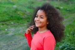 Hübsches Mädchen mit dem langen Afrohaar im Garten Stockfoto