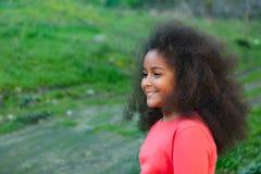 Hübsches Mädchen mit dem langen Afrohaar im Garten Lizenzfreies Stockbild