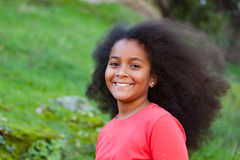 Hübsches Mädchen mit dem langen Afrohaar im Garten Stockfotos