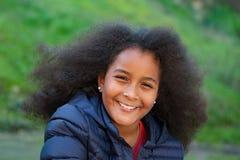Hübsches Mädchen mit dem langen Afrohaar im Garten Lizenzfreie Stockbilder