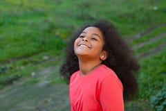 Hübsches Mädchen mit dem langen Afrohaar im Garten Lizenzfreies Stockfoto