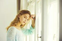 Hübsches Mädchen mit den blauen Augen, die am Fenster stehen stockfotos
