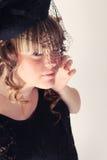 Hübsches Mädchen mit einem Hut und einem langen gelockten Haar Stockbild