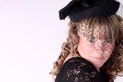 Hübsches Mädchen mit einem Hut und einem langen gelockten Haar Lizenzfreies Stockbild