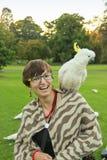 Hübsches Mädchen mit einem Papageien auf ihrer Schulter Stockfotografie