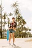 Hübsches Mädchen mit Skateboard auf der Straße Stockfotografie