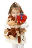 Hübsches Mädchen mit zwei Spielzeugaffen in den Händen Stockbild